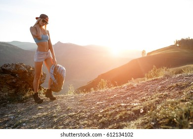 Girl tourist with backpack stand on mountainside background hill