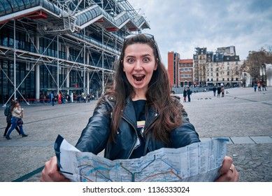Girl tourist with a card in hands in Paris