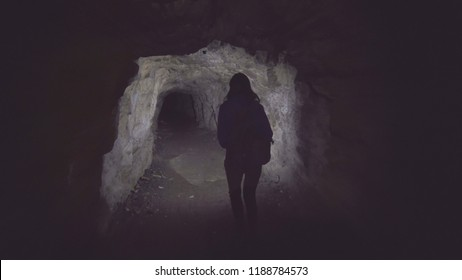 girl tourist is a cave with a flashlight from behind