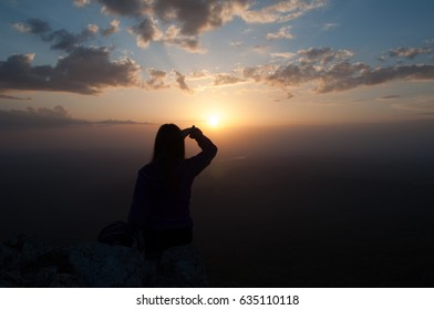 Girl in tourist clothes looking at the sunset from the mountain