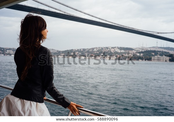 Girl tourist enjoying the view of the city from a boat. Cruise, tour, tourism. Background to the bridge. Soft focus and slight noise of the atmosphere for lifestyle.
