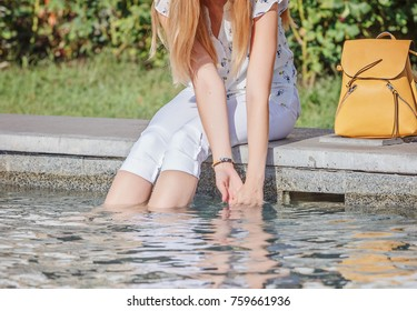 The girl is a tourist, her legs and hands are in the water / Girl sits on the edge of the fountain, putting her hands and feet there