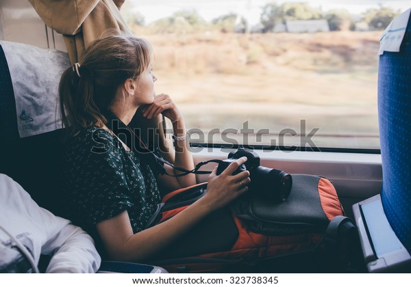 Girl tourist is looking out the window. fast train