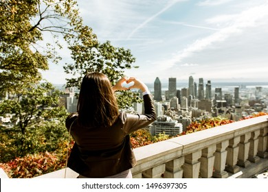 Girl tourist making heart shape with her hands, enjoying panoramic view of Montreal city skyline with modern skyscrapers and famous landmarks. Sending love greetings from Mont Royal