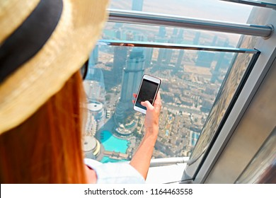 Girl tourist with mobile phone by the window of skyscraper of the Burj Khalifa in Dubai, United Arab Emirates, UAE. Close up