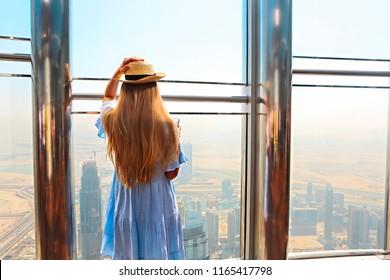 Girl tourist with mobile phone by the window of skyscraper of the Burj Khalifa in Dubai, United Arab Emirates, UAE