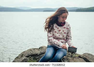 girl tourist prepares food on a gas burner in a saucepan against a background of water and mountains