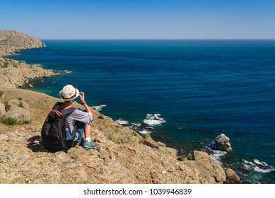 Girl tourist sits on the coast and admires the sea and mountains, view from the back