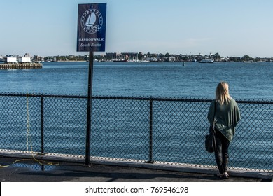 Girl Tourist standing near post sign Boston Harbor panorama walk isolated on a sunny summer day Long Wharf