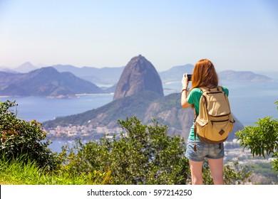 girl tourist taking a photo on a smartphone Pao de Acucar. Rio de Janeiro. Brazil