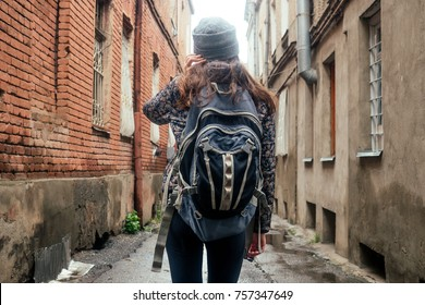 girl tourist walking down the street on the back of a backpack