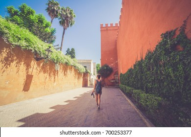 girl tourist walking in the street of the old quarter of Santa cruz in Sevilla, Spain