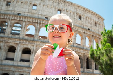 Girl Tourist Wearing Italian Flag Sunglasses And Holding Heart In Front Of Colosseum, Rome, Italy
