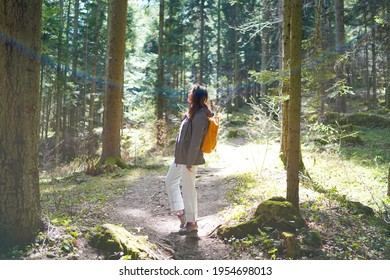 Girl tourist with yellow black backpack is walking on forest trail in mountains. Back view. Concept of wild adventure trekking in nature. Hipster young woman. Traveler on stroll in a remote location