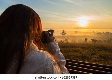 Girl tourists are taking a picture of the sunrise over a mountain in one of the most popular parks for viewing the sunrise of Thailand.
