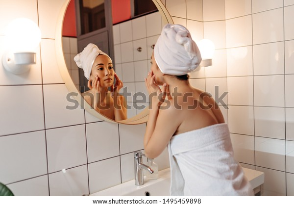 Girl in towel after shower looks in mirror in bathroom and does face massage
