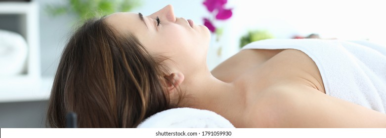 Girl in towel lies at reception massage therapist. Way to improve your health and well-being. Relieve muscle tension after heavy physical exertion or difficult day. Girl closed her eyes relaxing