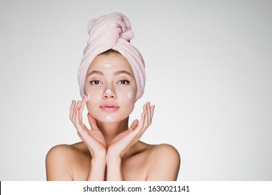 a girl with a towel on her head with bare shoulders applies cream to her face gently touching her cheeks with her fingers. gray background