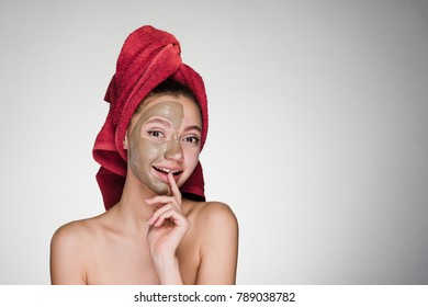 girl with a towel on her head smiling applying mask on face