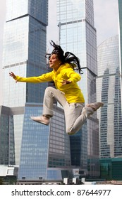 girl in a tracksuit jumping on the background of a big city