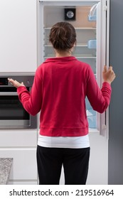 Girl in tracksuit opening the empty refrigerator