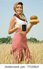 Girl in traditional clothes with bread and kvass at wheat field
