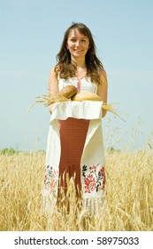 Girl in traditional clothes with bread  at wheat field