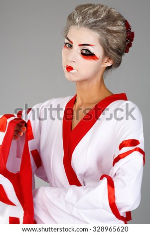 41bf2bb036 girl in traditional Japanese costume and makeup standing with hand raised  studio shot