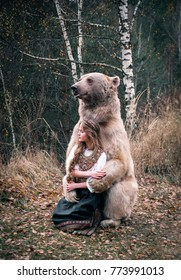 A girl in the traditional Russian dress hugging a real brown big bear in the picturesque forest