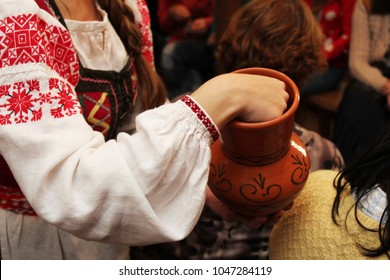 the girl in a traditional Slavic suit with a jug