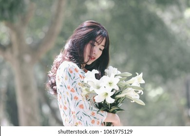 The girl in traditional Vietnamese dress with lily flowers in April every year in Hanoi, Vietnam.