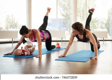 A girl with a trainer makes a swing with her foot while her baby lies on the rug