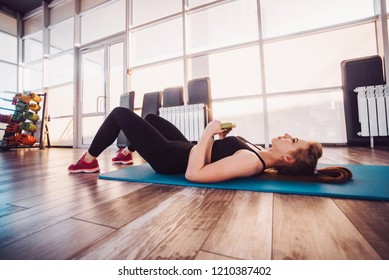 The girl is training in fitness gym and does various exercises. concept of a healthy lifestyle and exercise in the gym. The girl does abdominal crunches during training.
