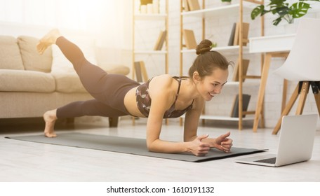 Photo of Girl training at home, doing plank and watching videos on laptop, training in living room