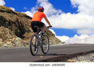 Girl training on a bike on mountain road