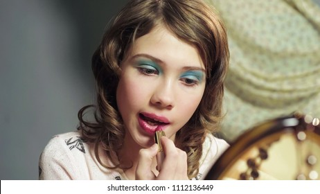 Girl of transitive age clumsily putting mothers lipstick on face, adolescence