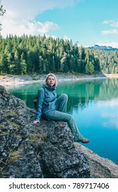 Girl travel on blue lake Chro Jezero in mountains alone in Durmitor Zhablyak, Montenegro. Autumn weather, calm scene. Backpacker walking outdoors, view over landscape