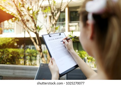 girl travel and rent short term condo in europe. concept of traveler looking for place to live sunny day, focus on doc. close up portrait of woman hands signing rental agreement on background of