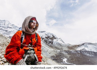 Girl traveler in hood and red, woolen sweater, wearing sunglasses, on the way in the Himalaya mountains, Nepal.