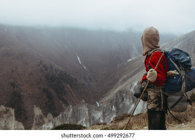 Girl traveler in hood and red, woolen sweater, on the way in the Himalaya mountains, Nepal.