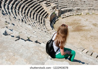 Girl traveler in the old nice Lykia town Mira looks at the amphitheater