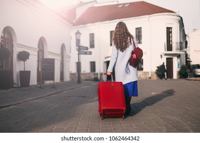 Girl traveler with a red suitcase. Walk around the city.