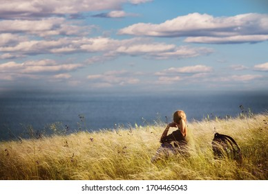 Girl traveler sits with her back on a cliff near the lake with a view of the natural landscape.