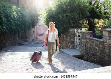 Girl traveler with suitcase at narrow italian street. Woman tourist is searching apartment, housing. Concept of student travel, summer vacation, solo female tourism, trip.