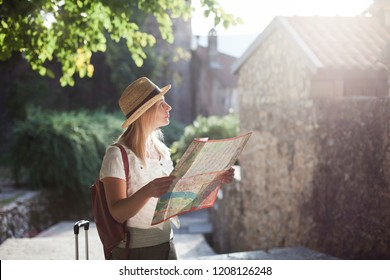 Girl traveler is using city map at town street. Woman tourist is searching direction, exploring locations, walking in magic light. Concept of travel, vacation, female tourism, adventure, trip, journey