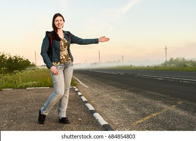 Girl traveler is voting with an open hand on the side of the road copyspace