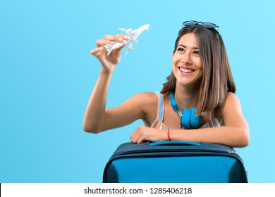 Girl traveling with her suitcase and holding a toy airplane on blue background