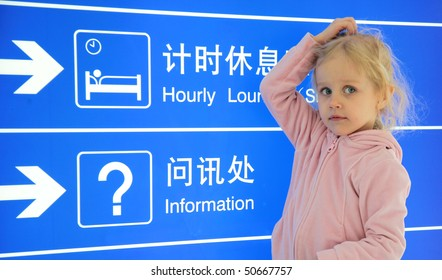 A girl traveling looking atinformation sign