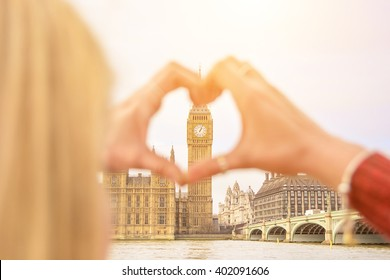 Girl traveling show love for London city making heart with her fingers on Big Ben Tower. Emotional concept of happy exclusive lifestyle moment, sharing time, discovering new place. Travel photography.