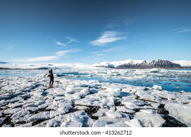 A girl traveller is looking at the view of Jokulsarlon Glacier Lagoon, Iceland